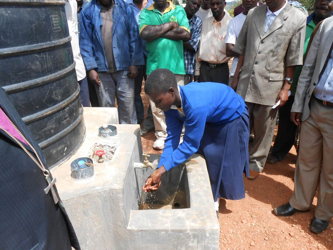 A student demonstrates using a new handwash station outside the latrine block